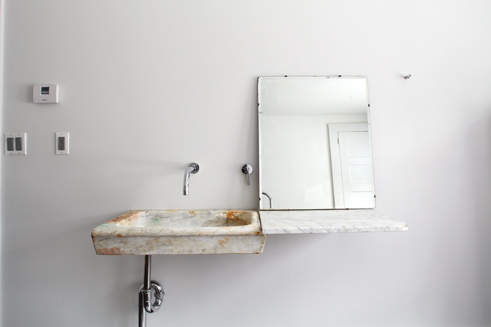 Bath Room, Wall Mount Sink, and Marble Counter In the guest bathroom, Givone installed a hand-chiseled sink made of 17th-century marble quarried from the hills outside of Rome.  Photo 10 of 12 in Hope Floats