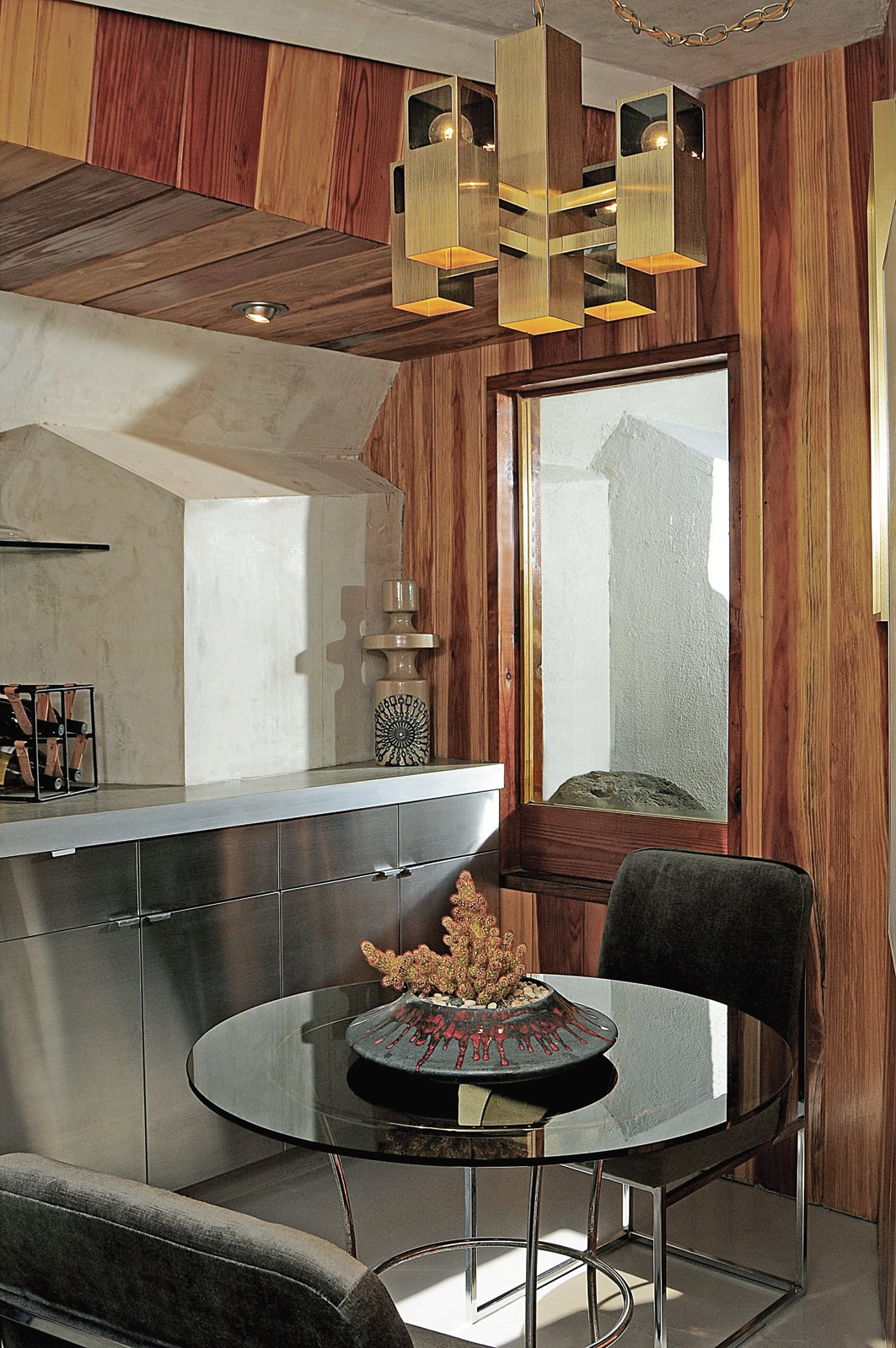 Dining Room, Table, Chair, and Pendant Lighting The eat-in kitchen features poured-in-place concrete countertops and redwood wall paneling.  Photo 3 of 5 in John Lautner's Desert Rose