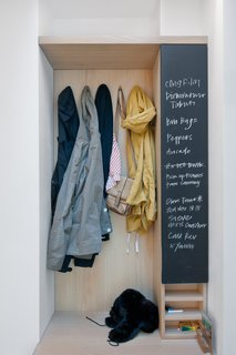 A built-in closet and chalkboard surface in the entry keeps things tidy and the couple's to-do list in order.