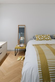 A peek inside the master bedroom, with touches of marigold yellow throughout.