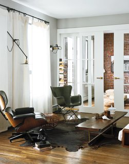 In the living room, an Eames lounge chair is matched with a Richard Conover–designed fiberglass chair in similar proportions. A custom coffee table by Asher Israelow complements the industrial lighting by Workstead, affixed to walls painted in Farrow and Ball's Manor House Gray. The sliding doors leading into the home office were fabricated by Markus Bartenschlager.