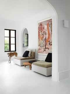 "Two pieces from E15's Shiraz sofa flank the company's wooden Leila side tables. Hill chose to use flat paint in Benjamin Moore's Decorators White throughout the home because it emphasizes the chalkiness of the plaster walls, making them ""look almost like slate."" The sconce shown in the foreground—David Chipperfield's Corrubedo design for FontanaArte—gives off a soft glow and replaces the dozens of paper-lampshade wall fixtures the owners found in the house when they bought it. Stewart Cohen's zany photograph of a gun-toting Marfa resident encapsulates Barbara Hill's offbeat brand of decorating: bright and minimal, yet darkly humorous."