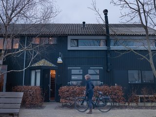 """Leen and Middendorp's home faces the Akkrum marina. In the spring and summer, the family can hear the chirping of birds that lay their eggs on the roof, in nests fortified with stray bits of wool that have floated into the garden. """"I like to picture the different colored nests up there,"""" says Leen. """"It gives me a feeling of harmony with nature."""""""