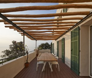On the patio, robinia wood beams shade a Kettal Vieques dining table and set of Moroso Supernatural chairs.