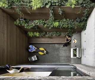 The dramatic 90-square-foot patio features a cooking and seating area. The floor and countertop are clad in Inca Gray Honed slate from Stone Source and the bench and planters are teak. By creating a vertical garden, Lubrano and Ciavarra integrated greenery into the views from every level of the house.