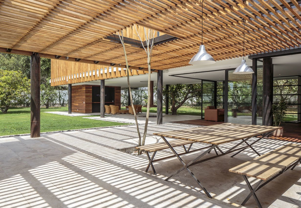 """Outdoor, Large Patio, Porch, Deck, and Concrete Patio, Porch, Deck Roberto Burneo designed this home for his eldest niece, her husband, and their three young children in a suburb outside Quito, the capital of Ecuador. The house is set on a flat expanse of land with fruit trees, and Burneo's design """"guides the social areas inward in order to link them to the gardens.""""  Photo 5 of 9 in Longer Days Call For More Time on These 9 Modern Porches from Uncle Knows Best"""