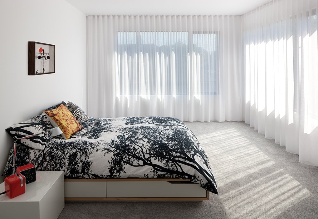 In the master bedroom, a Mandal bed from Ikea is draped with a Tuuli duvet cover by Marimekko. Tagged: Bedroom and Bed.  Photo 8 of 9 in An Industrial Designer's House Blends Economy and Simplicity