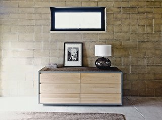 The earth bricks are a dominant visual element in the master suite, which is furnished with a dresser from Room & Board.