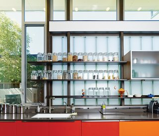The red- and orange-painted cabinets are meant to reflect sunlight and represent the heart of the home. The glass-fronted cabinets in the kitchen are by Henrybuilt, and the clear containers with dry goods are from the Container Store.