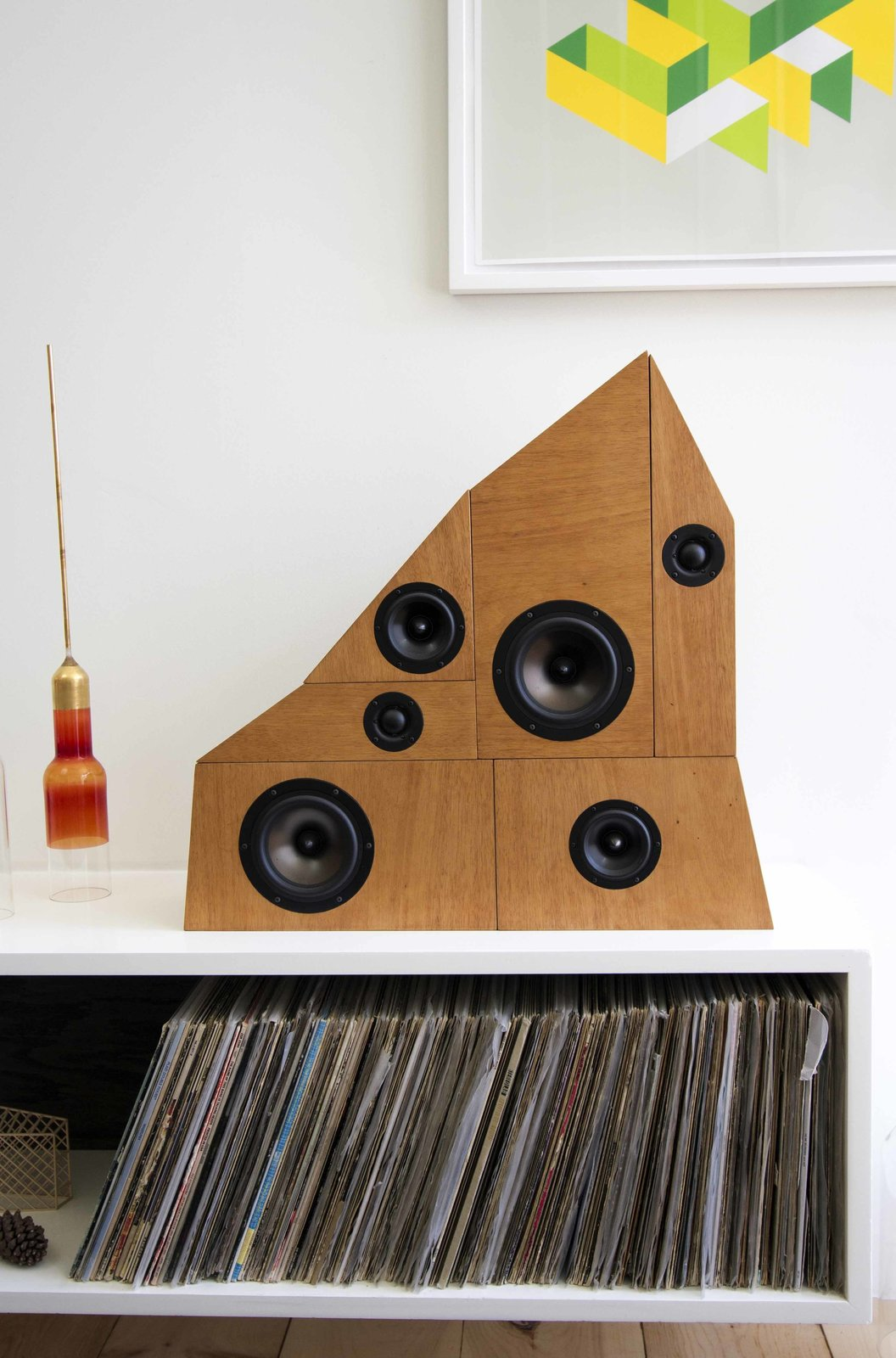 The architect designed and made most of the furniture for the house in the workshop in his garage, including the sofa, coffee table, kitchen lights (which were water-jet cut from a single piece of aluminium), and the speaker stack, which he based on the ramshackle piles of old stereo equipment commonly found in thrift store Hi-fi Corners.  Photo 4 of 9 in Home and Studio Maximizes Very Narrow Site in Echo Park