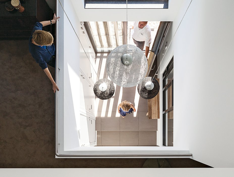 Hallway Inside, just off the entrance, pendant lights from Woonfabriek hang in the triple-height central hall.  Photo 4 of 13 in A Modern Take on the Pitched-Roof