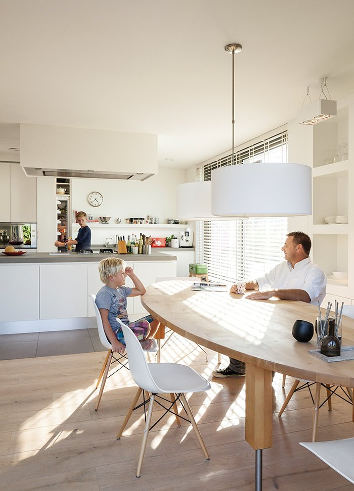 """Kitchen, Light Hardwood Floor, Granite Counter, and Pendant Lighting The kitchen of a home on an Amsterdam canal """"is where it all happens,"""" says Van Zeijl. As the hub of the home, the room is situated at the front of the house and features a minimal palette and Belgian granite countertops. The table is by Pilat & Pilat and the pendants are from It's About Romi.  Photo 5 of 13 in A Modern Take on the Pitched-Roof"""