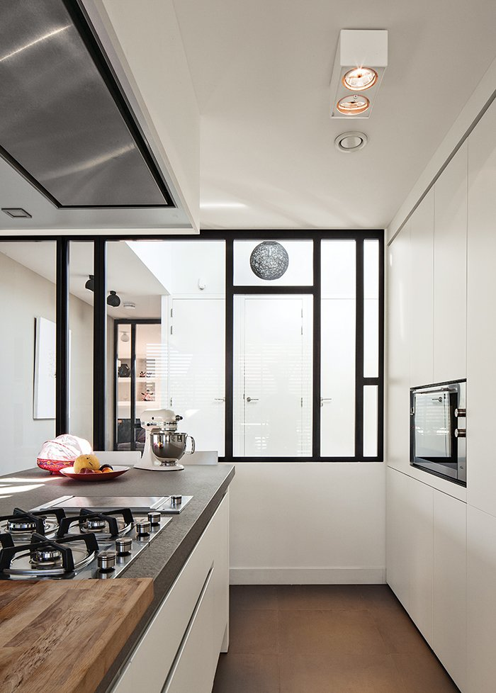 """Kitchen, Cooktops, Ceiling Lighting, and Microwave With a custom design by Scalo, the kitchen is """"white and simple; we didn't want handles,"""" notes De Graaf. The hotplate, oven, and teppan-yaki grill are from Falliss.  Photo 6 of 13 in A Modern Take on the Pitched-Roof"""