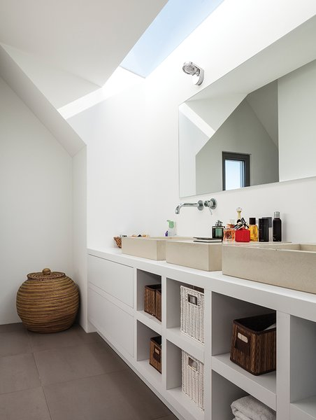 Bath Room, Vessel Sink, and Wall Lighting Similar architectural geometries are at play in the ceiling of a bathroom, where custom sinks by Concr3te accompany Grohe fixtures.  Photo 12 of 13 in A Modern Take on the Pitched-Roof