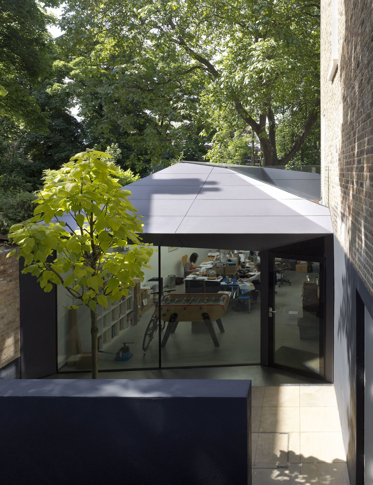 """Exterior, Metal Siding Material, and House Building Type Backyard excavation created a sunken courtyard, where the side entrance to a new 750-square-foot office space lies. The exterior is clad in Corian, a surface normally found on countertops. """"The clients love that they can go to another wing of the house and have an office,"""" says Brooks. """"There's a physical seperation. We've designed it so in the future, if they close the firm, they can open up the door between the office and the dining room and connect the entire basement floor.""""  Photo 2 of 7 in Victorian Home in London Gets a Modern Office Addition"""