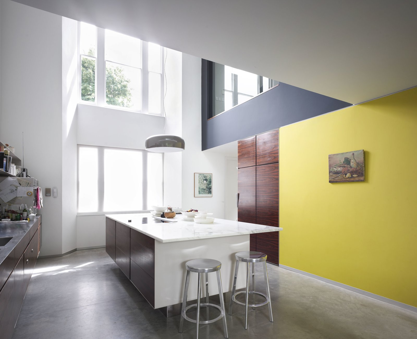 The kitchen features a concrete island topped with marble. Deja-Vu stools by Naoto Fukasawa surround the island. A print by Guy Gormley, as well as a painting bought during holiday in St. Tropez, hang on the walls. Tagged: Kitchen, Concrete Floor, Marble Counter, Pendant Lighting, Wood Cabinet, Cooktops, and Metal Counter.  Photo 6 of 7 in Victorian Home in London Gets a Modern Office Addition