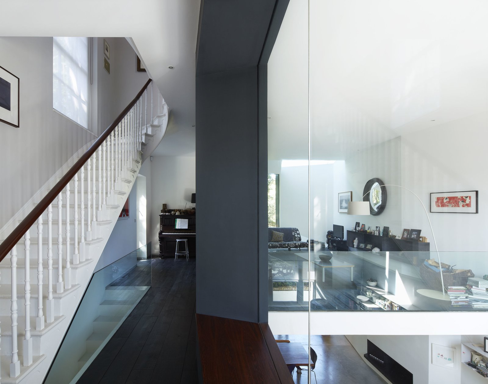 Dark Hardwood Floor, Staircase, Wood Railing, and Wood Tread On the mezzanine level, different styles and eras complement each other, from the Georgian staircase to the sheets of glass and the Lola Convex Mirror to the James Irvine sofa.  Photo 7 of 7 in Victorian Home in London Gets a Modern Office Addition