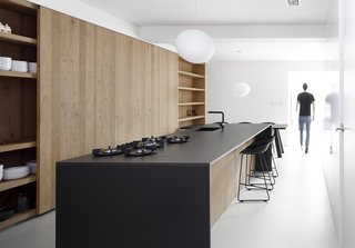 The kitchen island is made of oak with a thin, black stone countertop.