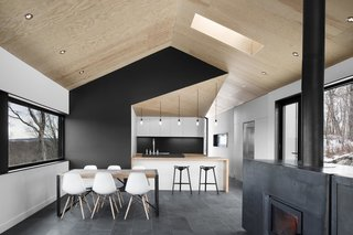 """The architects stuck to a gray-scale color palette, installing slate tile floors that softly contrast with the white walls and Eames dining chairs. """"It lets the views out the windows become the focus,"""" Dworkind explains. Doses of pure black accent important features, like the central wall that divides the kitchen and master bedroom behind it from the main living space."""