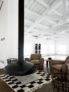 In the upper-level seating area, an Ergofocus fireplace is flanked by a pair of leather armchairs designed by Navone for Baxter