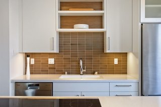 Earth tone tiles back a Kohler sink at this energy efficient home in Davis, California. The backsplash is from Heath Ceramics, the sink is Kohler, and the custom millwork is by Schmidt's Cabinetry.