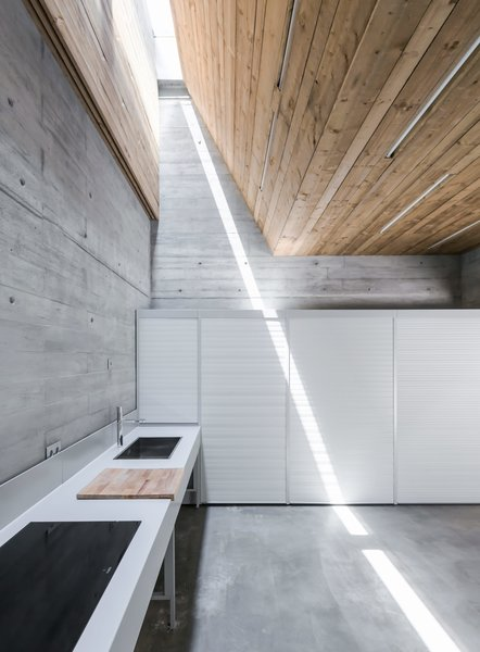 House in Matosinhos is a minimal home located in Matosinhos, Portugal, created by nu.ma.  The lot, where the house is inserted, has a non-regular shape, longitudinal, and perpendicular to the street Nossa Senhora da Conceição. It was important to keep the alignment of the house with the existing buildings in order to avoid formal irregularities within the street development. The interior spatial distribution is separated by function and by floors. Due to the longitudinal nature of the lot, the architects proposed an internal yard at the center of the home to allow for natural light to enter the dining/living room and kitchen.  Photo 8 of 8 in Spotlight on Portugal: 7 Epic Modern Spaces
