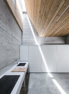 Sunk into a slope beside a stream in Portugal's Caniçada Valley, the rear of this vacation retreat's ground floor is deeply removed from the outdoors. Fortunately, architecture firm Carvalho Araújo found a way to direct natural light into the kitchen by pairing a skylight with a double-height funnel. The narrow band provides just a modicum of illumination, but it's a potent reminder of the scenery on high.