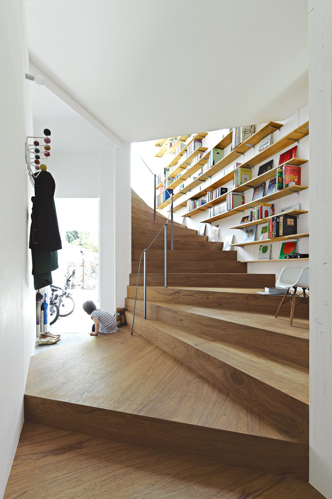 Staircase, Metal Railing, and Wood Tread Bookshelves add extra utility to the undulating staircase in Tokyo's 921-square-foot Coil house. The space was designed by architect Akihisa Hirata for Sakura and Ryo Sugiura, a young couple with two children.  Photo 3 of 3 in This Sculptural Staircase Shapes an Entire Home