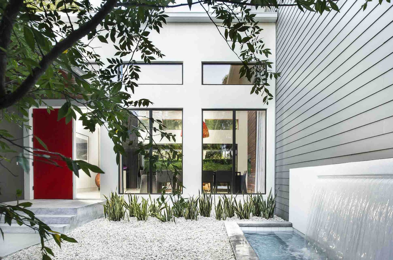 Outdoor, Small Pools, Tubs, Shower, Concrete Pools, Tubs, Shower, and Front Yard The red door was De Azevedo's idea, says Phil Kean, president of the Phil Kean Design Group. It adds a spash of color to the front courtyard, which is simply landscaped with gravel and low-maintenance plants. A water feature was installed next to the James Hardie fiber-cement siding.  Photo 2 of 7 in A Modern Home For a Design-Savvy Family in Florida