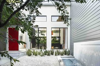 The red door was the homeowner's idea, says Phil Kean, president of the Phil Kean Design Group. It adds a splash of color to the front courtyard, which is simply landscaped with gravel and low-maintenance plants. A water feature was installed next to the James Hardie fiber-cement siding.