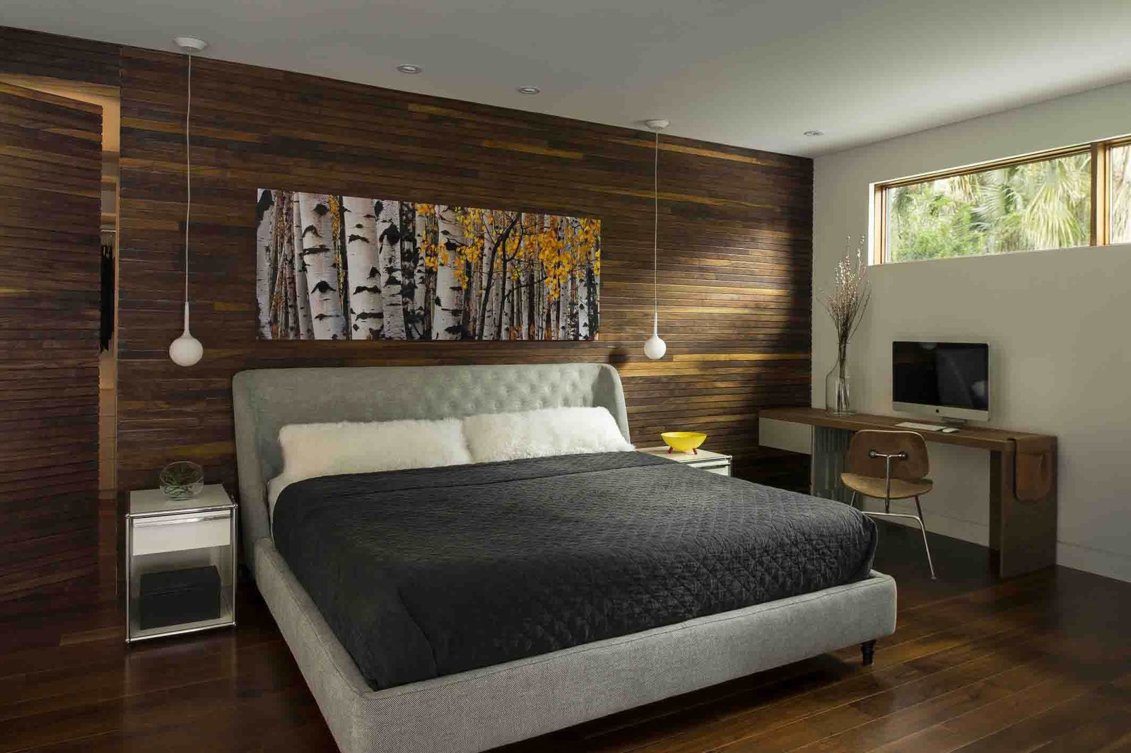 """Bedroom and Bed Wood was used more extensively in the master bedroom. """"I think the intention was just to warm it up and make it more cozy,"""" Kean says. A wood-covered """"disappearing door"""" cleverly conceals a closet.  Photo 6 of 7 in A Modern Home For a Design-Savvy Family in Florida"""