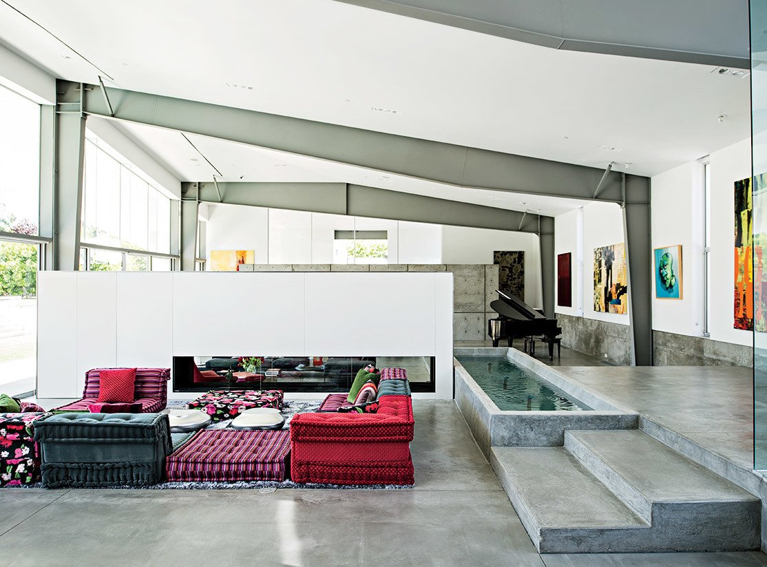 A Mah Jong sofa by Roche Bobois in the living room lends a colorful counterpoint to the custom water feature that runs alongside it. Tagged: Living Room, Sofa, Ottomans, Coffee Tables, Recessed Lighting, and Ceiling Lighting.  Innovative Homes from Our Prefab Issue by Allie Weiss from An Energy-Efficient Hybrid Prefab Keeps Cool in the Palm Springs Desert
