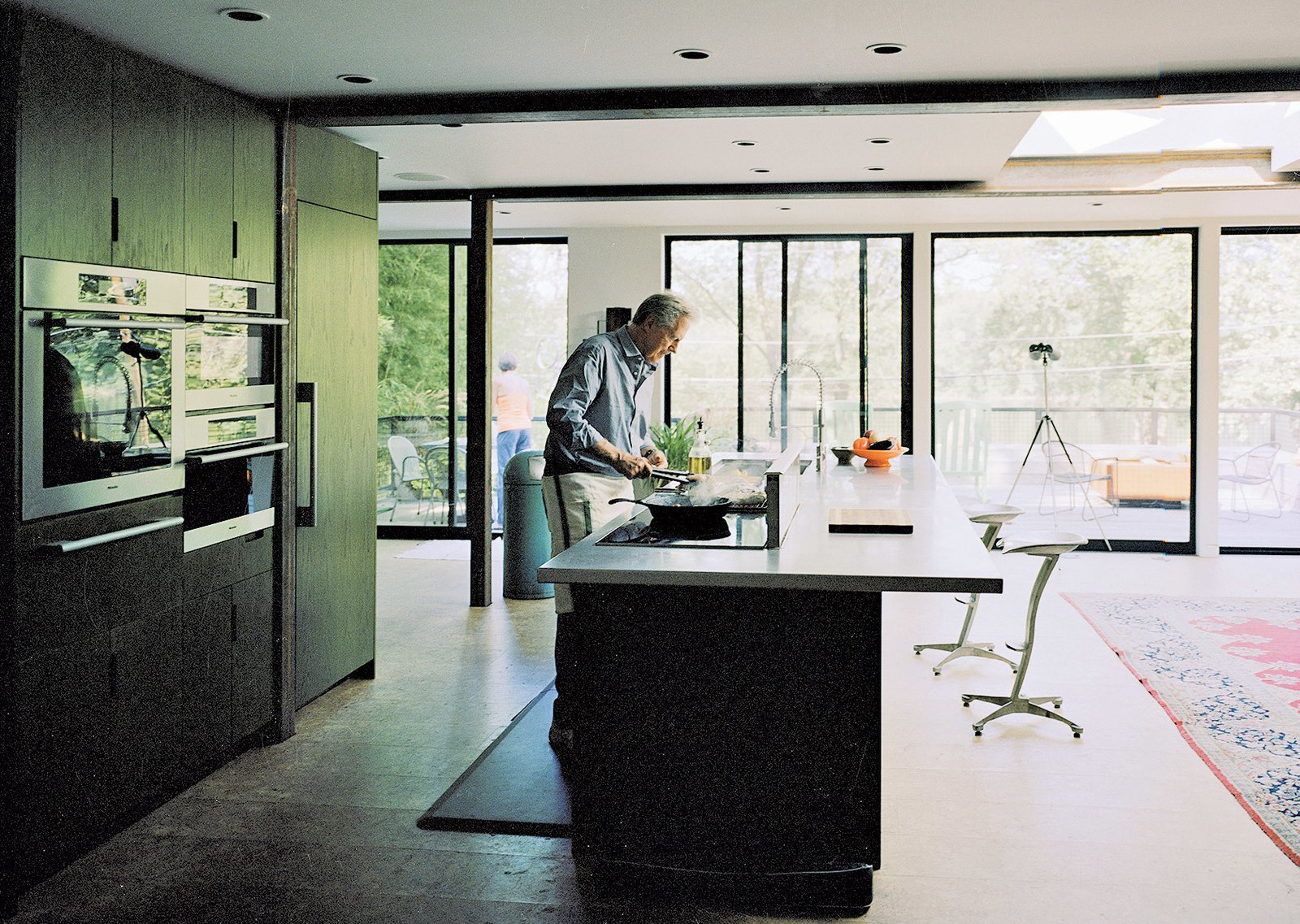 Kitchen, Cooktops, and Wall Oven The custom kitchen boasts a suite of appliances by Miele and custom sliding doors and windows by Arcadia Architectural Series that open to views of the Delaware River, just across the street.  Photo 5 of 12 in A Shipping Container Home in Pennsylvania Embraces Its Rugged Industrial Origins