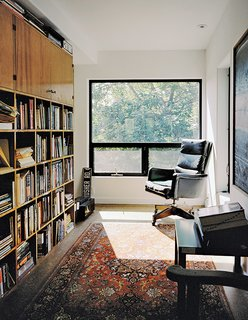 In homeowner Bill Mathesius's office on the third floor, an antique armchair, a rug, and a bookshelf made from salvaged wood create a cozy, sun-filled reading nook.