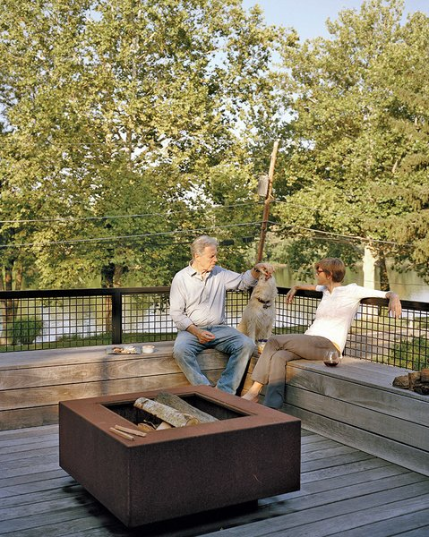 The staggering of the shipping containers created a series of decks in the rear of the home, which overlooks the Delaware River. A mix of vintage finds and pieces designed by Mathesius, including a Cor-Ten steel fire pit on the second-floor deck, furnish a majority of the home.