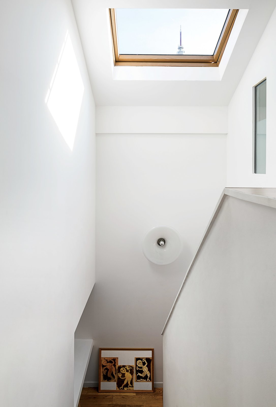 """The antenna of Claude Vasconi's TDF television tower is visible through the Velux skylight architects Caroline Djuric and Mirco Tardio added to a family house in France. """"It's very French, very angular,"""" Djuric says of the renovation. The light fixture was found at a brocante, or vintage market.  Photo 2 of 7 in Now That's How You Double Your Square Footage"""