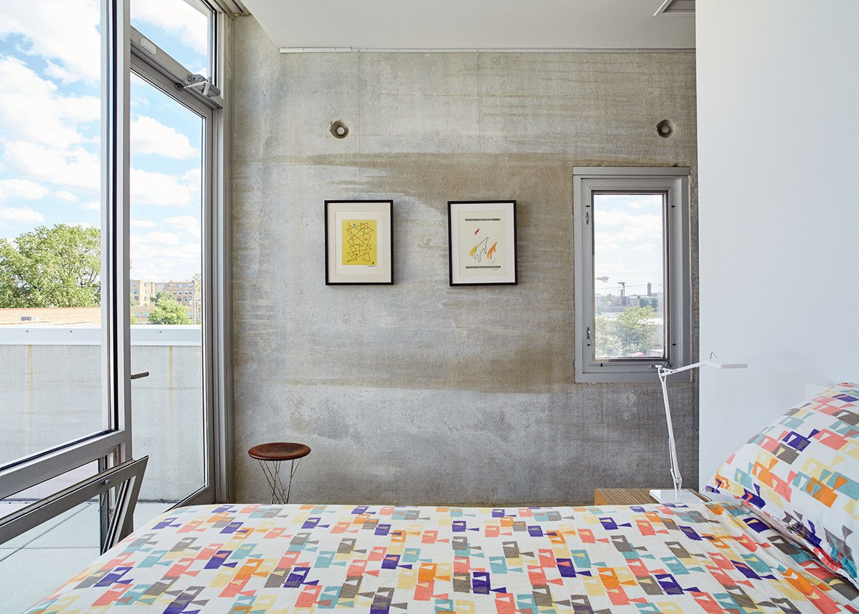 The raw concrete panels serve as a backdrop for the couple's design collection. The bedroom features a Rocking Stool by Isamu Noguchi for Knoll and a Kelvin lamp by Antonio Citterio for Flos.  Photo 9 of 9 in In Just 48 Hours, a Chicago Live/Work Space Is Built from the Ground Up Using Concrete Panels