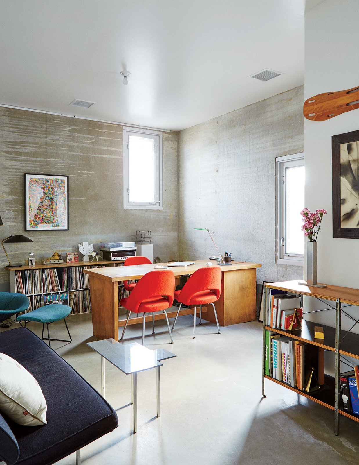 Office, Lamps, Desk, Chair, Storage, Shelves, Bookcase, and Concrete Floor The office is a showcase that includes an Eames Storage Unit for Herman Miller, a wall-mounted Eames leg splint, and chairs by Eero Saarinen and Harry Bertoia for Knoll.  Photo 8 of 9 in In Just 48 Hours, a Chicago Live/Work Space Is Built from the Ground Up Using Concrete Panels