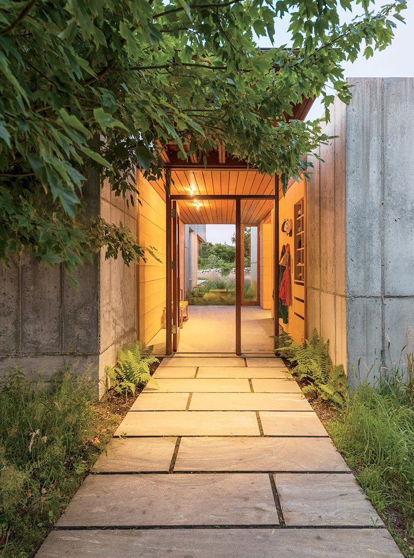 Doors and Exterior A palette of stone, concrete, and greenery greets guests at the home's front entrance.  Photo 7 of 11 in Six Concrete Boxes Make a Jaw-Dropping Martha's Vineyard Home