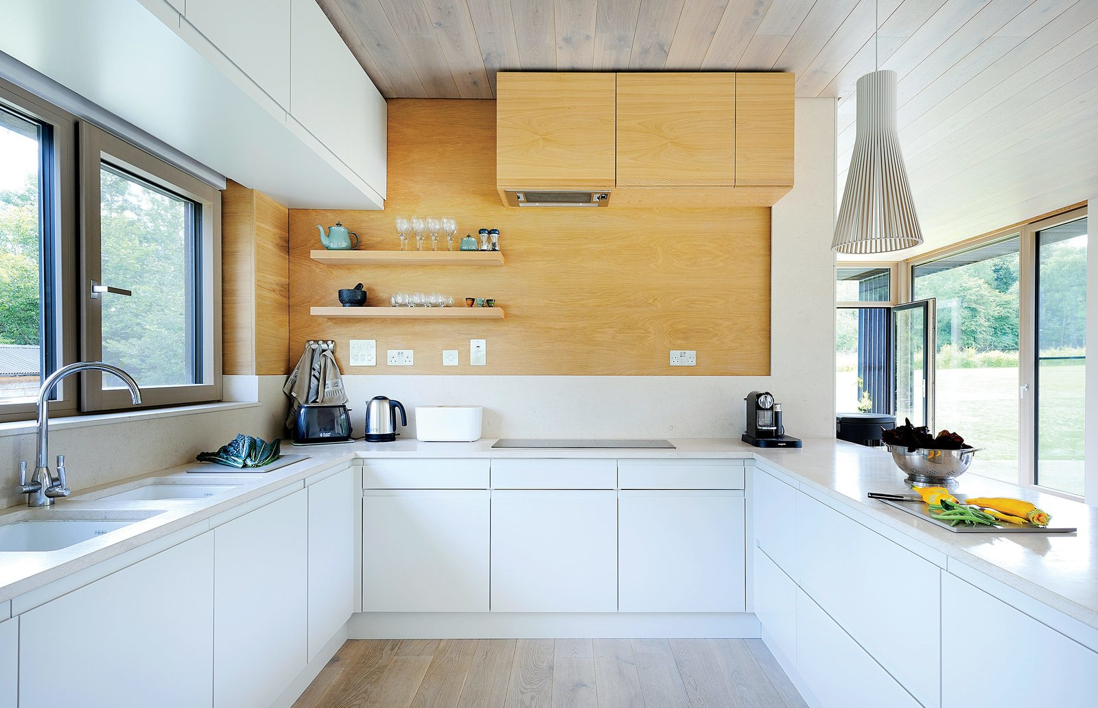 Bright interior finishes, including whitened oak on the floor and ceiling and Kitchen Collection's Malmo cabinets in porcelain and oak colorways, were installed off-site.  Photo 3 of 3 in A Modern Mobile Home Dropped in Place by Crane
