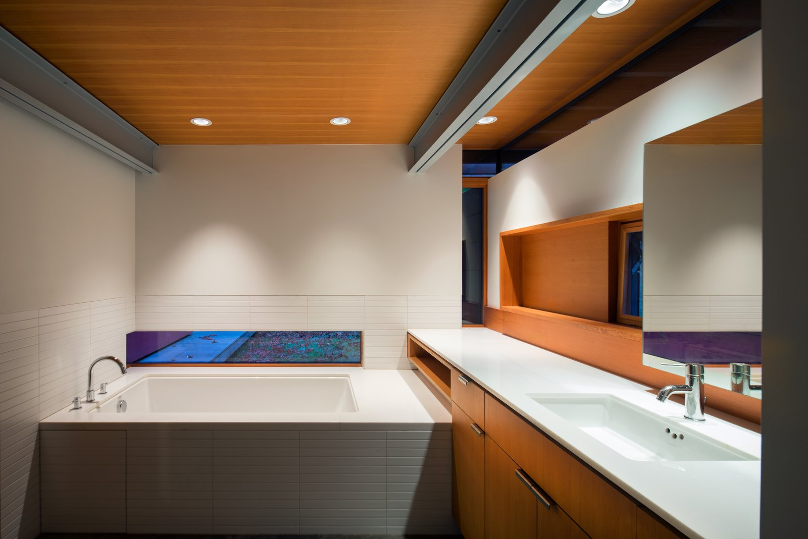 Bath Room A horizontal sliver of window allows light into the bathroom, with tile by Ann Sacks, a Zuma Collection C Series tub, a Kohler tub filler, and an Elkay faucet.  Photo 13 of 16 in An Off-the-Grid Island Home for a Seattle Music Producer