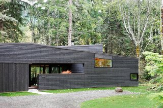 """30 All-Black Exterior Modern Homes - Photo 1 of 30 - """"From the street, it appears as a rectangular building with sloping shed roofs, but this is actually an illusion,"""" Hutchison notes. """"The floor plan is actually U-shaped, wrapping around an entry courtyard that is contained by the continuous west facade."""" A standing seam metal roof by Custom Bilt Metals blends in with the cedar siding."""