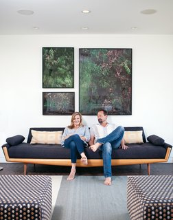 Gabbert and Avery relax on a vintage sofa in their living room beneath large-format photos of juniper bushes by Maegan Hill-Carroll.