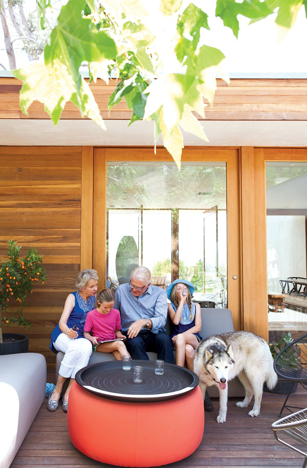 Daughters Ingrid and Jane catch up with their grandparents on the Room & Board–furnished front deck.  Photo 1 of 4 in How to Throw a Great Party in Six Steps from L-Shaped Indoor-Outdoor LA Home