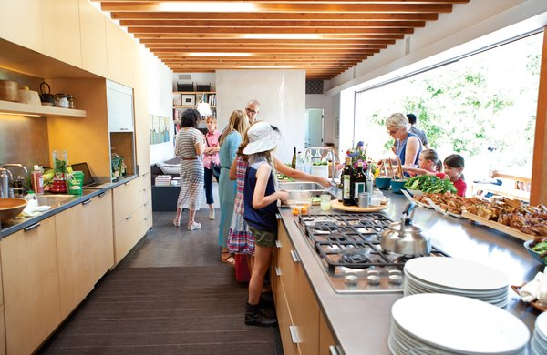 In the open-plan kitchen, bowls and platters by Heath Ceramics and bamboo trays and tongs from Design House Stockholm decorate the farm-to-table buffet on the steel-topped kitchen island.  Photo 4 of 4 in How to Throw a Great Party in Six Steps