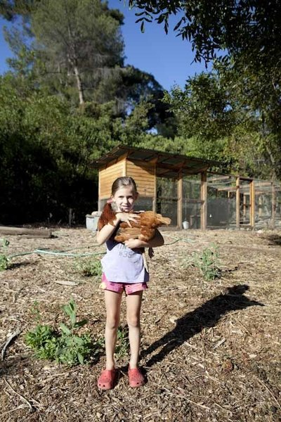 Ingrid shows off one of the chickens the family raises in their large and very productive coop.  Photo 16 of 21 in L-Shaped Indoor-Outdoor LA Home