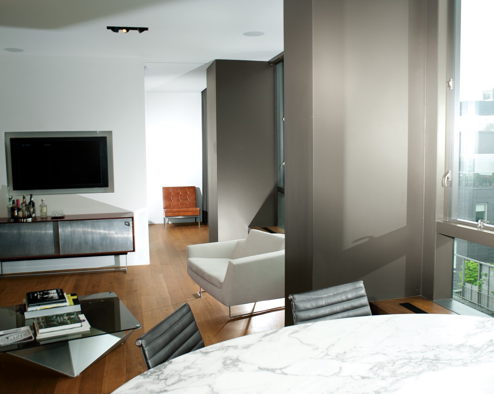 Living Room Architect Cass Calder Smith embarked on a gut renovation to join two apartments inside a SoHo building, resulting in a 1,600-square-foot residence. He redid the floors in oak and redesigned the wall of windows that frames views to the east.  Photo 5 of 14 in High-Rise Living in Manhattan