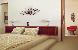 A McKenzie-designed bed and a retro wall-hanging in one bedroom.