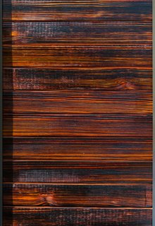 The charred-wood siding, inspired by shou sugi ban, comes in various stains, such as cherry (shown here). The blow-torching technique helps with resistance against insects, rot, water, mold, and fire.