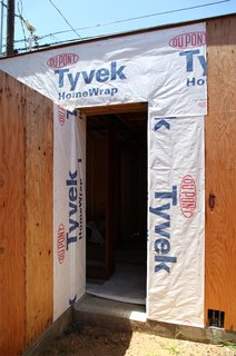 Dupont Tyvek weather barrier covers the wall near a doorway. Tyvek flashing will be added prior to the door installation.